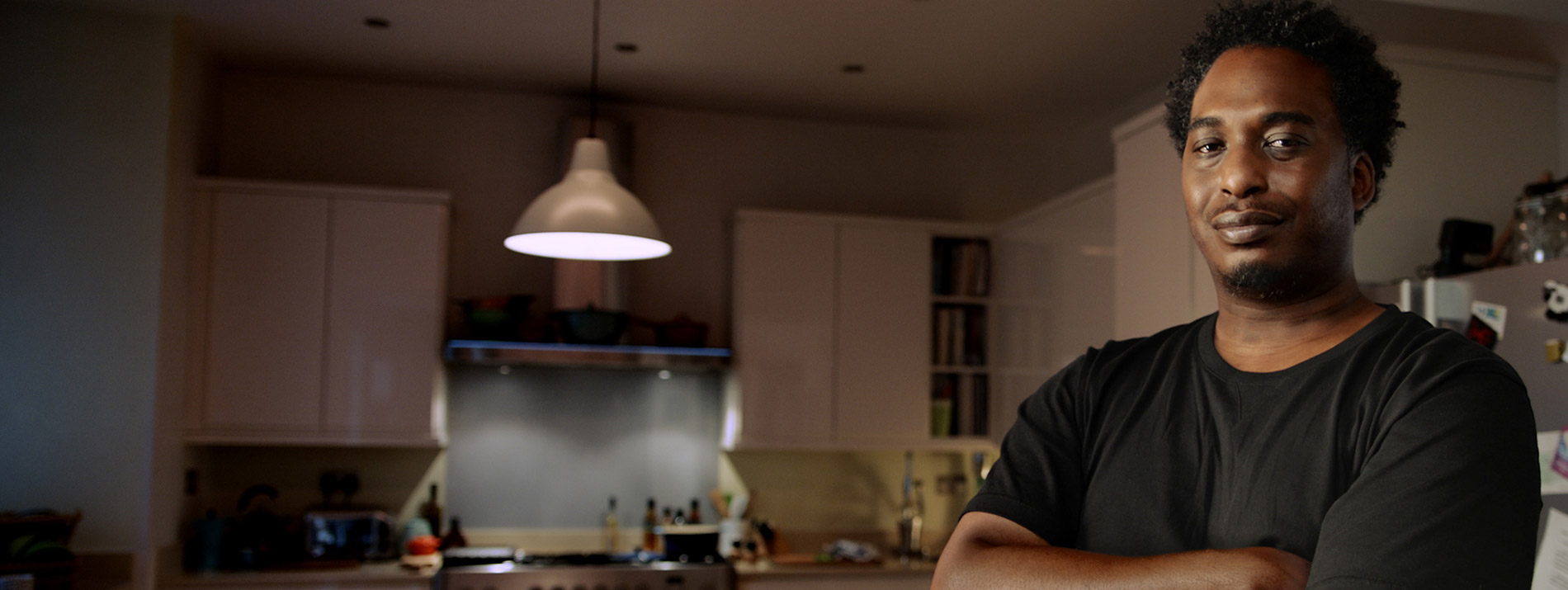 A smiling man standing in his kitchen.