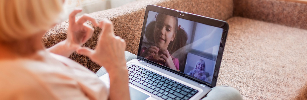 Woman making a heart gesture with her hands towards a video call with a young girl.