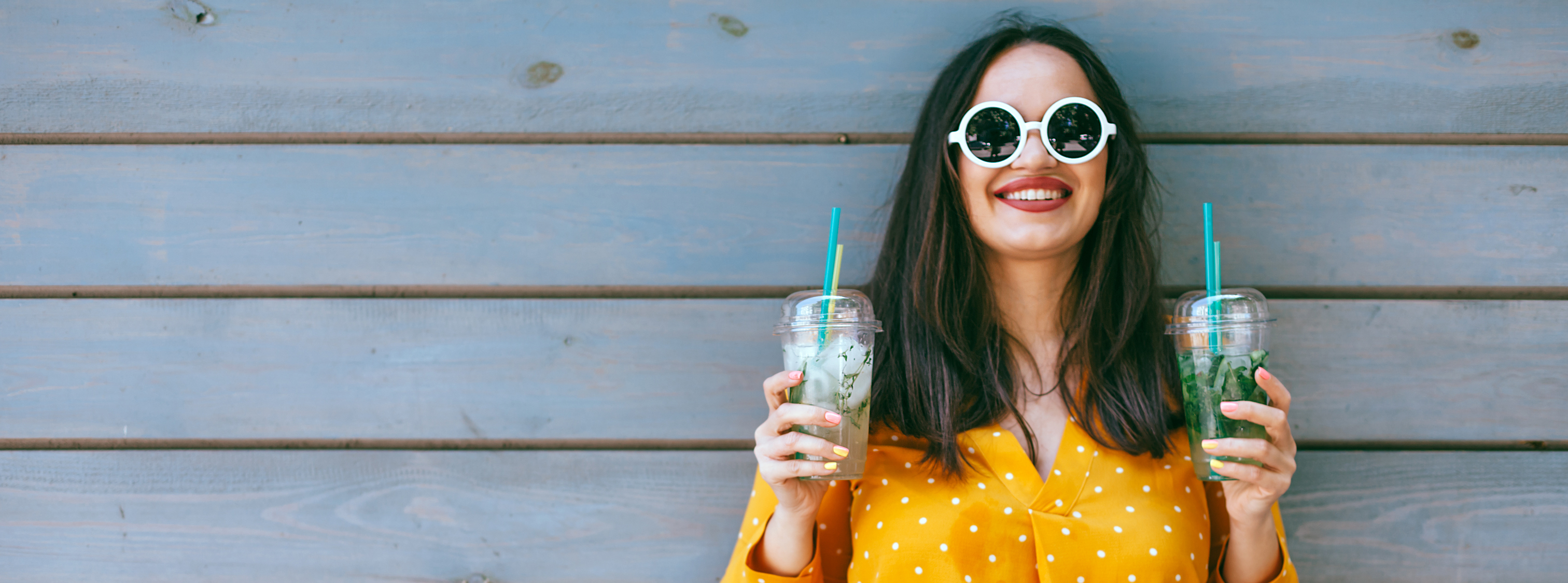 Smiling woman wearing sunglasses and holding two takeaway cups with two different drinks