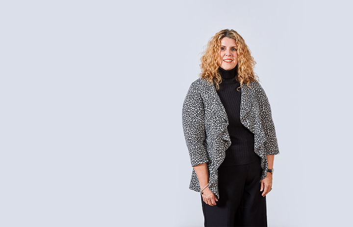 Curly-haired woman in a black dress with a spotted cardigan on top.
