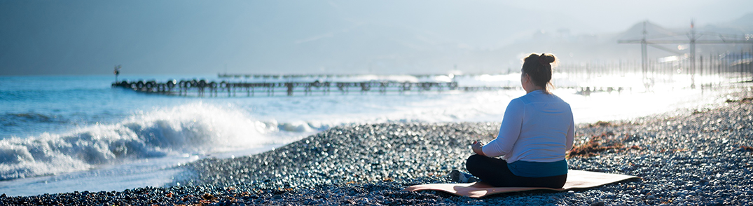 Woman sitting on the mat at the seashore having view on the big wave and  jetty