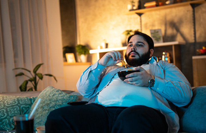 Man sitting on his couch eating chips from a bowl.