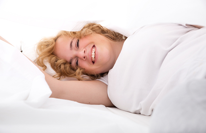Woman lying sideways on a bed smiling