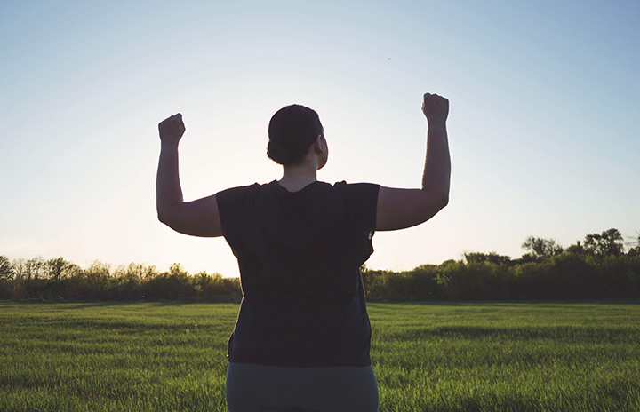 Woman in a black T-shirt is standing on a green meadow having her hands up in the air; clear blue sky, sun is rising