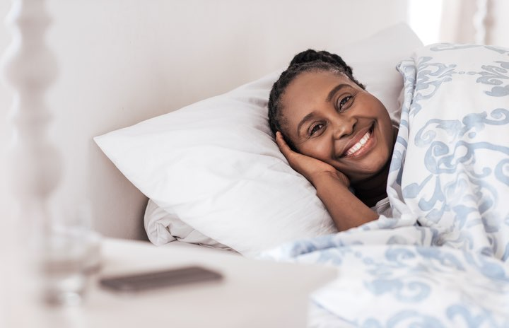 Woman lying in a bed and smiling